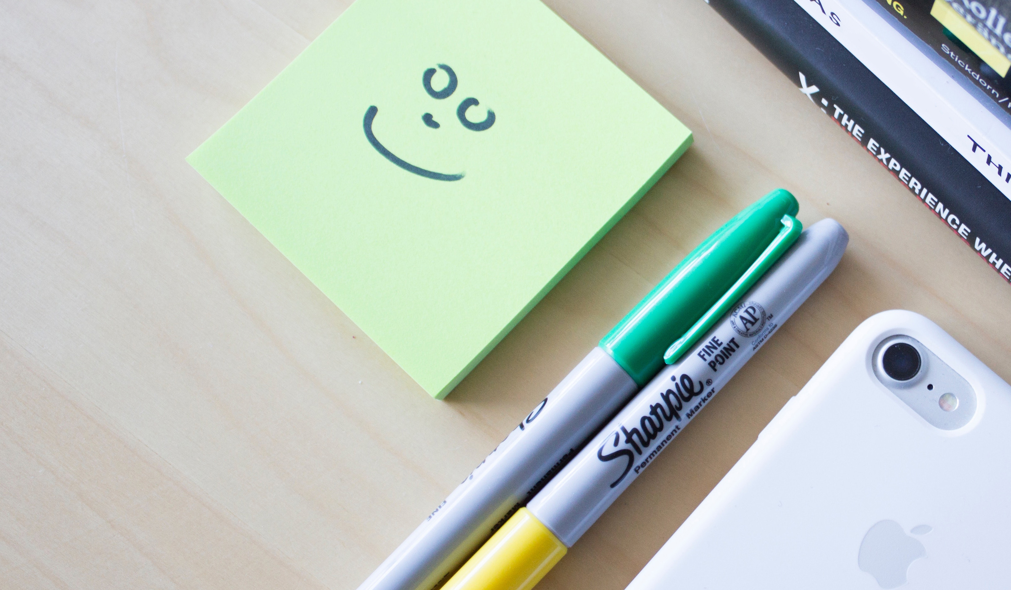 A pad of sticky notes, a stack of books, two pens and a mobile phone.