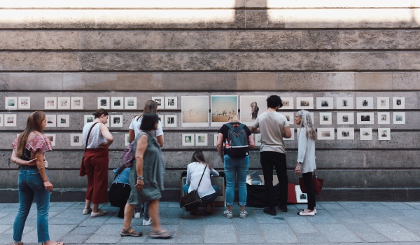 Community members look at a public art display on a sidewalk.