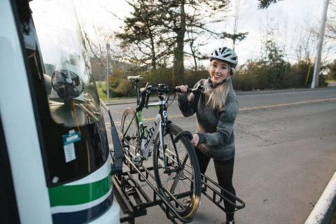 A woman secures her bike on the front of a BC transit bus