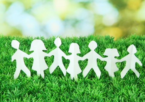 cutout human figures holding hands on a backdrop of green grass